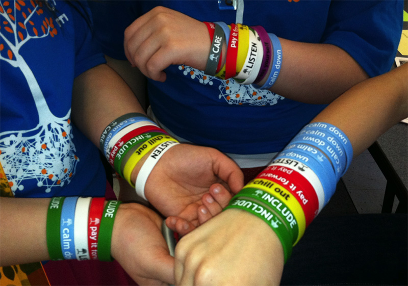 In addition to creating signs to promote the Roots Program, students wore colorful wristbands to spread the message. This photo was taken on Roots Day, a one-day festival in which students promoted Roots through print posters, other multicolored and Roots-themed wristbands, and even the T-shirts they wore.