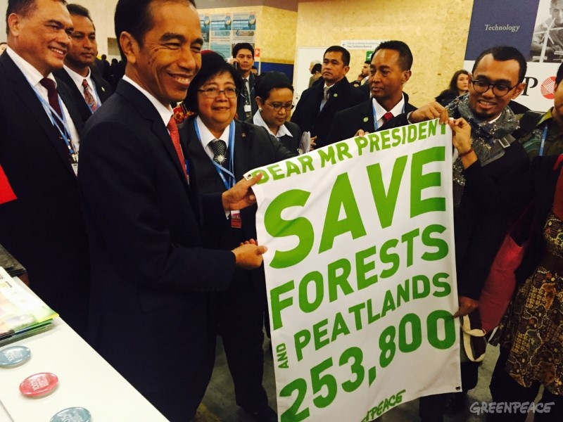 Indonesian President Joko Widodo (left) and Greenpeace campaigner Teguh Surya (in glasses) hold a banner referencing the support of 253,800 people for saving Indonesia's forests and peatlands at the climate talks in Paris in December 2015. Photo courtesy of Greenpeace