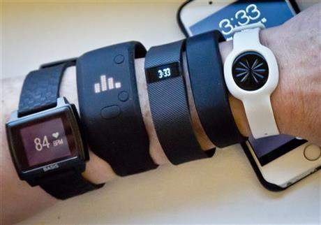 Fitness trackers, from left, Basis Peak, Adidas Fit Smart, Fitbit Charge, Sony SmartBand, and Jawbone Move, are posed for a photo next to an iPhone, Monday, Dec. 15, 2014, in New York.