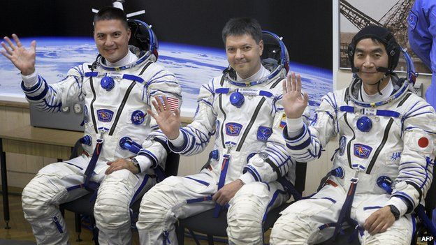 Kjell Lindgren, Kimiya Yui, and Oleg Kononenko sit together after docking with the ISS.