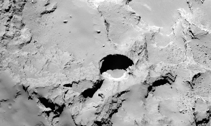 Photographs captured by Rosetta reveal actively-forming large sinkhole-like structures on the surface of comet 67P.