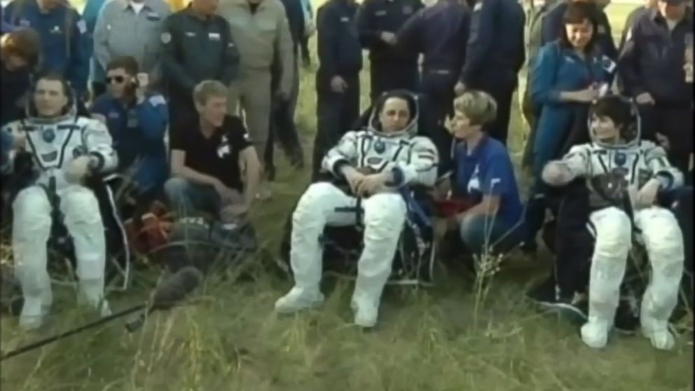 Three astronauts return to Earth after a 199-day stay at the International Space Station.
