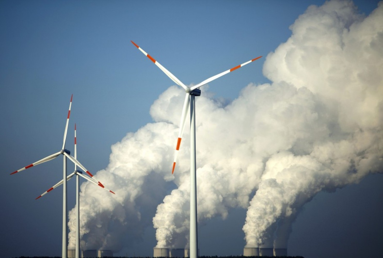 File photo of steam billowing from the cooling towers of Vattenfall's Jaenschwalde brown coal power station behind wind turbines near Cottbus, eastern Germany, Dec. 2, 2009. /Reuters)