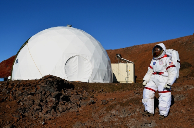 A HI SEAS participant in a simulated space suit standing outside the simulated Mars habitat