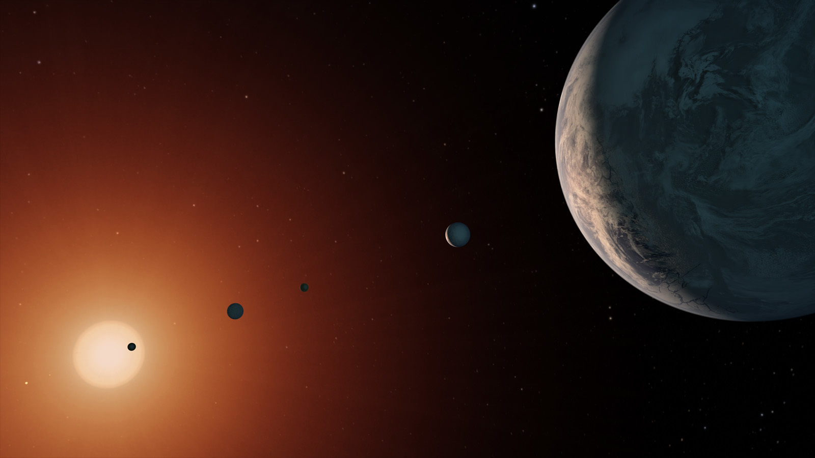 An artist's rendition of the TRAPPIST-1 system, in which seven Earth-like exoplanets orbit an ultra-cool red dwarf star at the center.