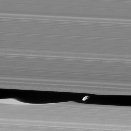A close-up of Daphnis and the waves it makes in Saturn's rings.