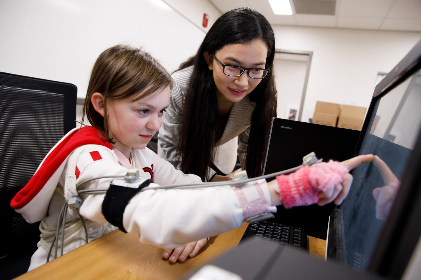 Di Wu directs a volunteer as she touches images on a screen using a device designed to track miniscule fluctuation in the arm's movement. Credit: James Brosher, Indiana University