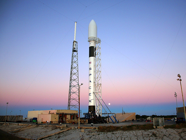 A SpaceX Falcon 9 rocket standing tall at a launch site.