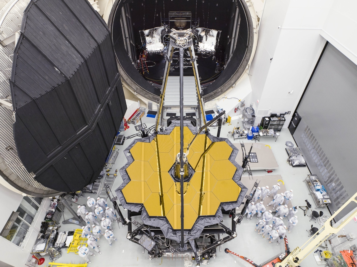 Engineers stand next to the massive heart of the James Webb Space Telescope after removing it from NASA's Chamber A testing facility in Houston, Texas.