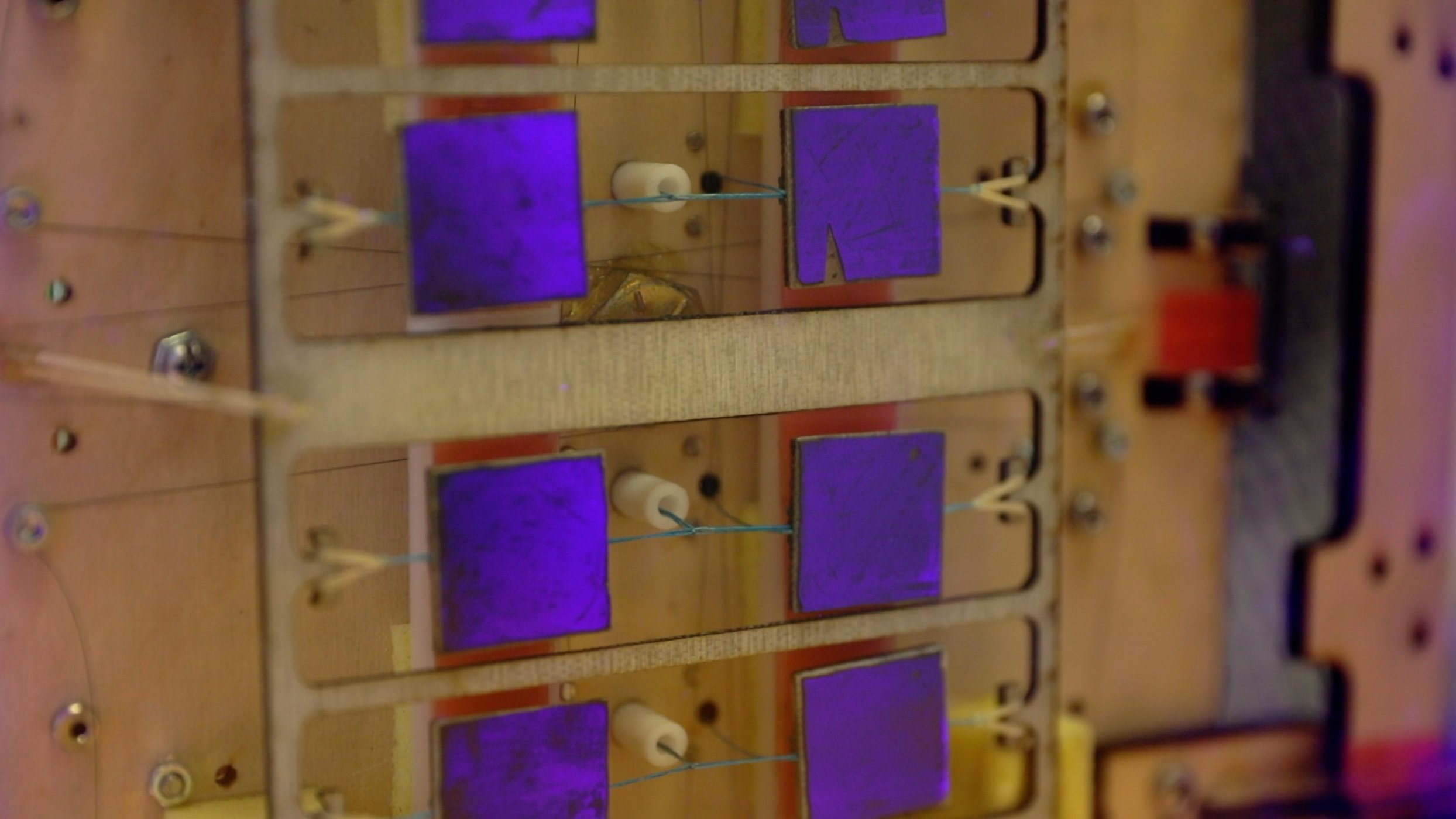 The purple squares are grippers using gecko-inspired physics to grab onto objects.