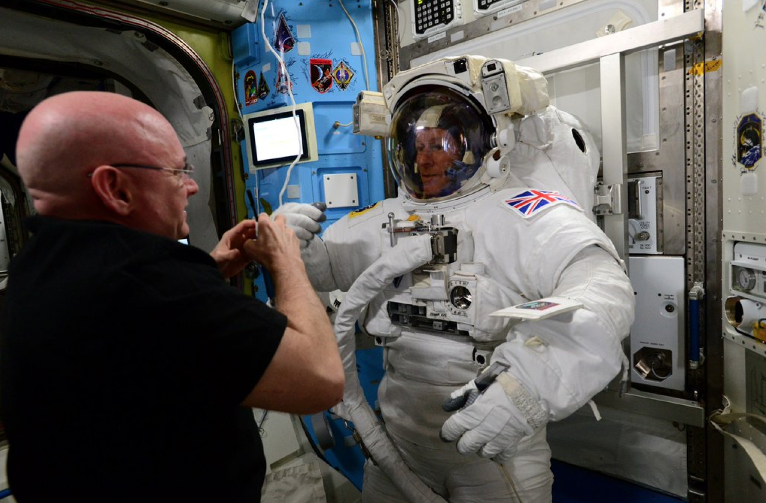 ESA's Tim Peake tries on his space suit with the help of Scott Kelly.