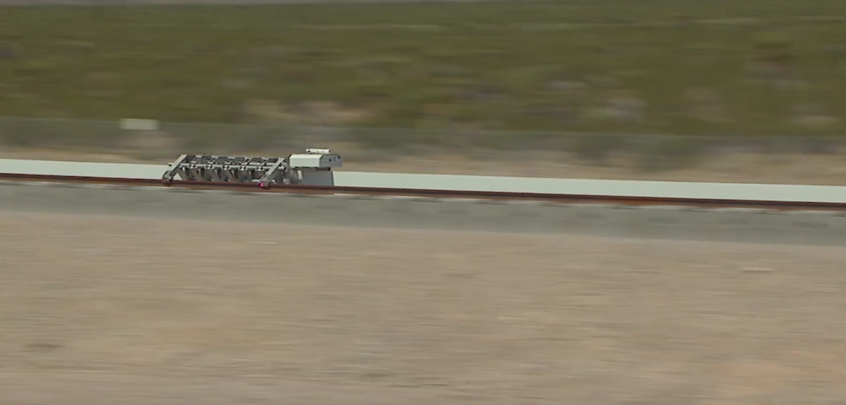 The Hyperloop One test vehicle flies down the tracks in the Nevada Desert.