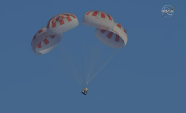 A photograph of SpaceX's Crew Dragon capsule falling from the sky with parachutes.