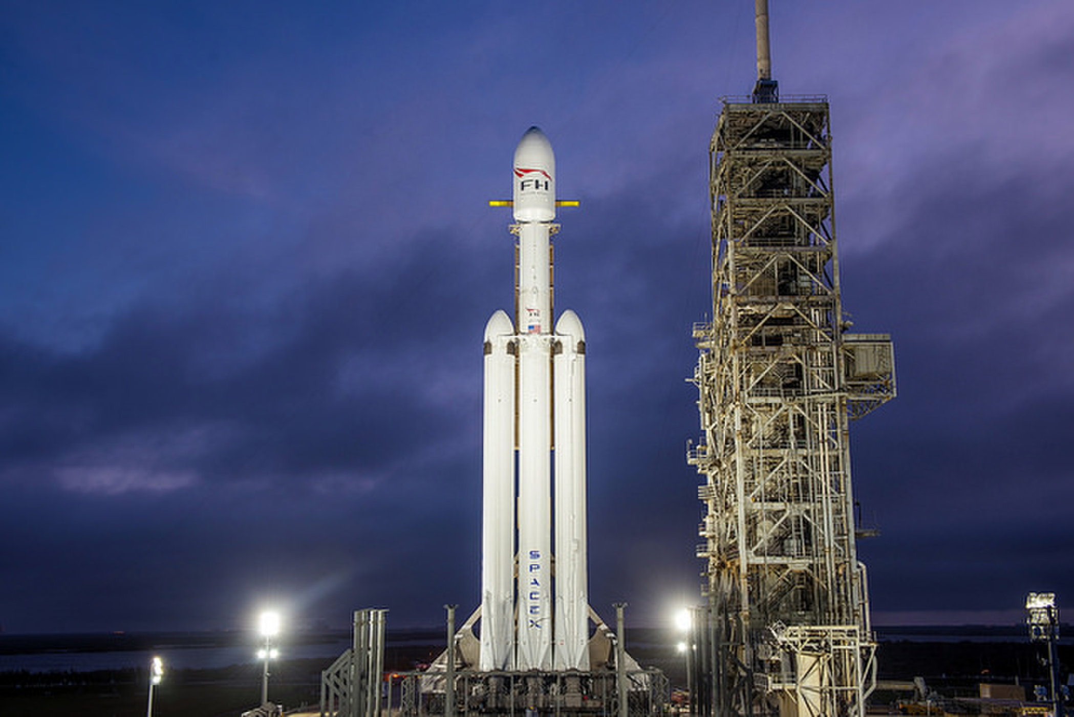 A night shot of the SpaceX Falcon Heavy rocket standing upright at NASA's launchpad 39A.