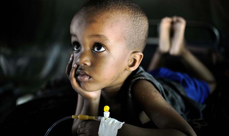 """""""The thing about malaria is that really, really poor people have it, so the medicine has to be very inexpensive,"""" says Spencer Knapp. """"We think that ours is going to be inexpensive."""" Above: Mohammed, suffering from Malaria, recovers at a Burundian run clinic in Somalia's capital, Mogadishu."""