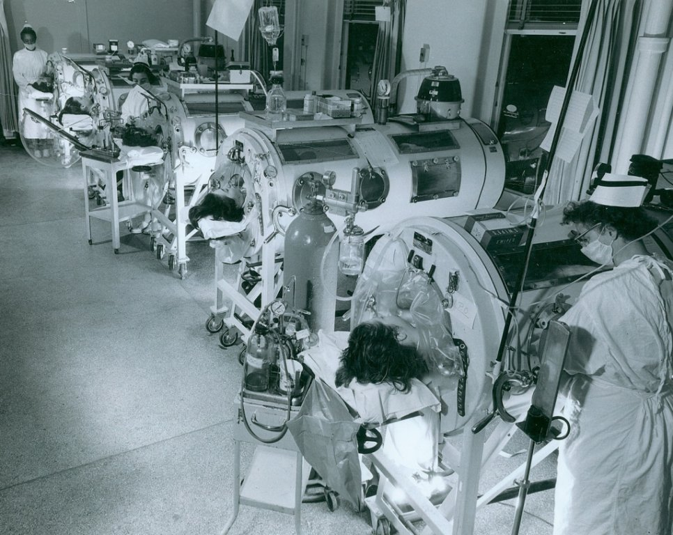 In the 1950s, the Iron Lung machines seen in this photo helped people breathe when polio virus killed their lung muscle cells