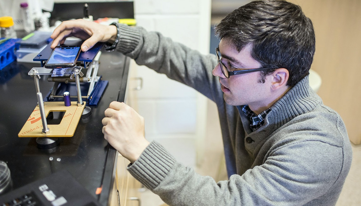 Kevin Yehl sets up a smartphone microscope to get a readout for the particle motion of the rolling DNA-based motor.