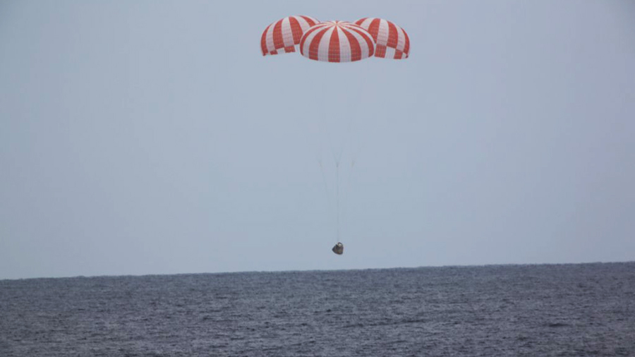 SpaceX Dragon spacecraft lands in the Pacific Ocean via parachute.