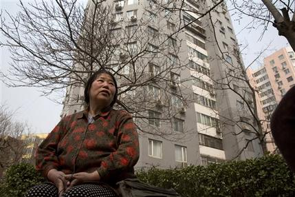 In this photo taken Monday, March 16, 2015, Chen Shuhong is interviewed in front of the residential compound where she rents out apartments as housing for cancer patients in Beijing. These so-called cancer hotels that dot the neighborhood around China's most renowned cancer hospital, give patients an affordable, cozy place to wait for appointments and undergo outpatient treatment.